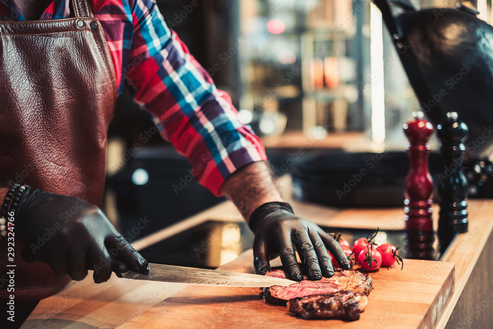 Fototapety, obrazy: Cutting freshly cooked beef steak on a wooden board
