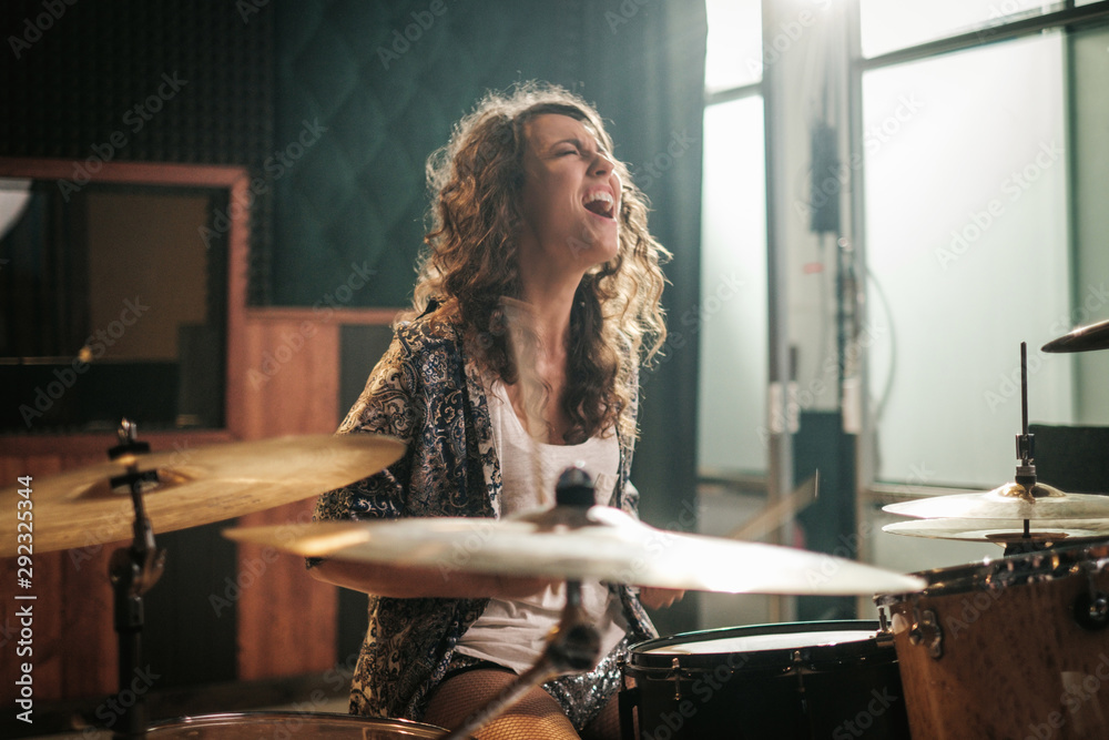 Fototapeta Woman playing drums during music band rehearsal
