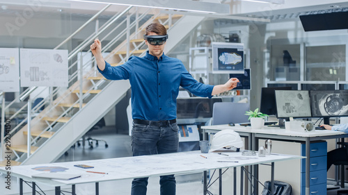 Photo Engineering Software Developer Wearing Virtual Reality Headset Uses Gestures to Interact with Augmented Reality while Designing Industrial Engine Model in Modern Facility