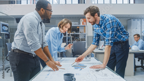 Obraz In the Industrial Engineering Facility: Female Designer Works with Industrial Engineer and Master Technician, They have Discussion, Analyse Engine Design Technical Drafts that are Lying on the Table - fototapety do salonu