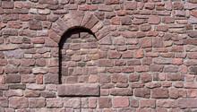 Rötliche Alte Mauer Mit Halbrundem, Zugemauerten Fenster Im Sonnenschein