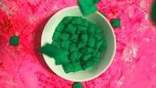 Abstract Slow Motion Video Of Green Flakes Falling Into A White Plate On A Pink Background, Top View. Breakfast, Cereal, Food, Kitchen Concept