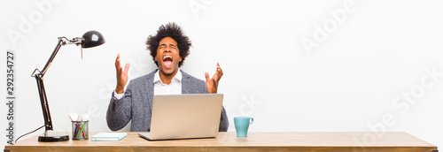 Fotografia young black businessman furiously screaming, feeling stressed and annoyed with h