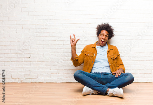 young black man feeling happy, fun, confident, positive and rebellious, making rock or heavy metal sign with hand sitting on the floor at home - 292355744