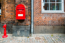 Red Fire Hydrant And Red Postal Box Against Brick Wall In Helsingor, Denmark