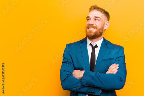 Fototapeta  young red head businessman feeling happy, proud and hopeful, wondering or thinki