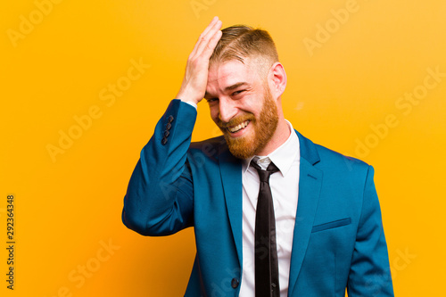 Valokuvatapetti young red head businessman laughing and slapping forehead like saying d'oh! I