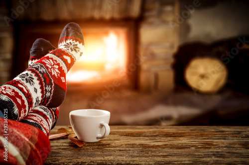 Fotomural Woman legs with christmas wool socks and fireplace