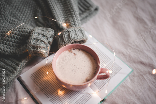 Foto op Plexiglas Chocolade Cute mug of coffee with Christmas lights on open book with knitted warm sweater in bed close up. Good morning. Breakfast. Winter holiday season.