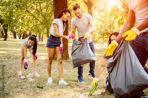 Photo Team of friends cleaning up the park by collecting litter into plastic bags