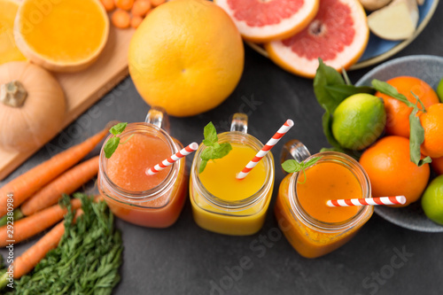 Fototapeta food , healthy eating and vegetarian concept - mason jar glasses of orange and carrot juices with paper straws, fruits and vegetables on slate table obraz