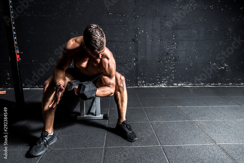 Photo Young strong muscular sweaty fit man biceps muscle workout cross training with h