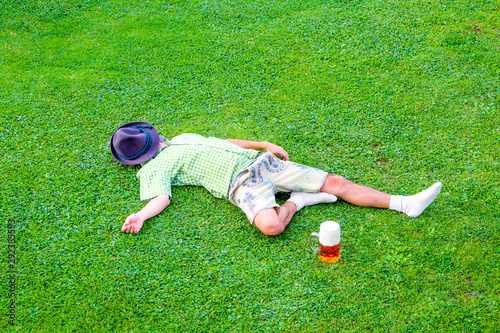 Fotografia, Obraz drunken bavarian men sleeps in the meadow