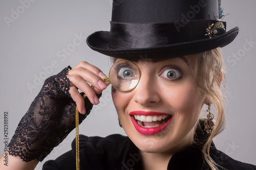 Fotografie, Obraz Beautiful blonde in an elegant vintage black dress, an elegant hat and a cigarette with a long mouthpiece