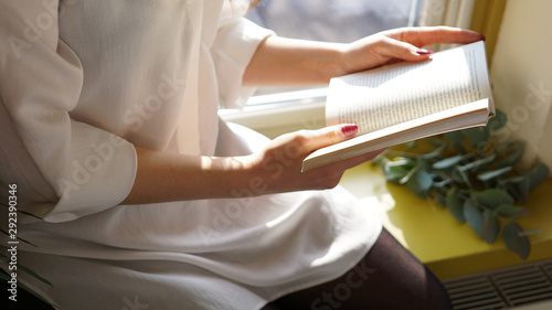 Canvas Prints Akt Woman reading a book by the windosill