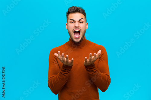 young hispanic man looking desperate and frustrated, stressed, unhappy and annoy Wallpaper Mural