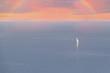 Sailboat at sea under a rainbow