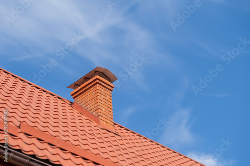 Canvas Print Red roof of a detached house and chimney against the blue sky, closeup