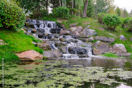 Foto op Plexiglas Bos rivier Landscape with a forest waterfall. Water runs on the rocks to the bottom forming a small pond.