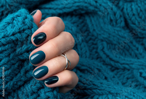 Fényképezés Manicured woman's hand in warm wool turquoise sweater