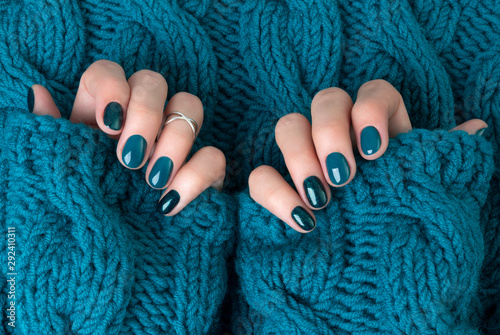 Leinwand Poster Manicured woman's hands in warm wool turquoise sweater