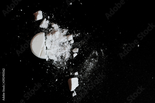 Photo White squashed tablet pill on black background. Top view