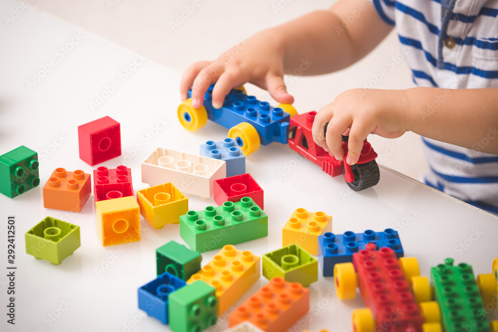 Fototapety, obrazy: Toddler child playing multi-colored cubes on the table. Colorful plastic bricks for the early development of the child. Early learning and educational toys for a little boy