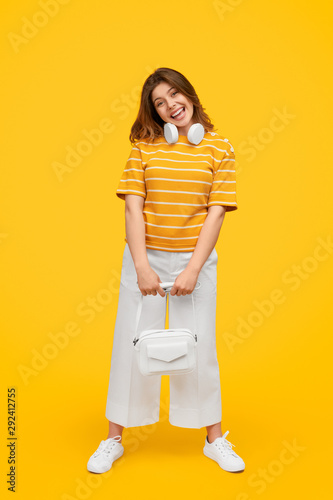 Playful woman with headphones in trendy outfit standing and looking at camera - 292412755