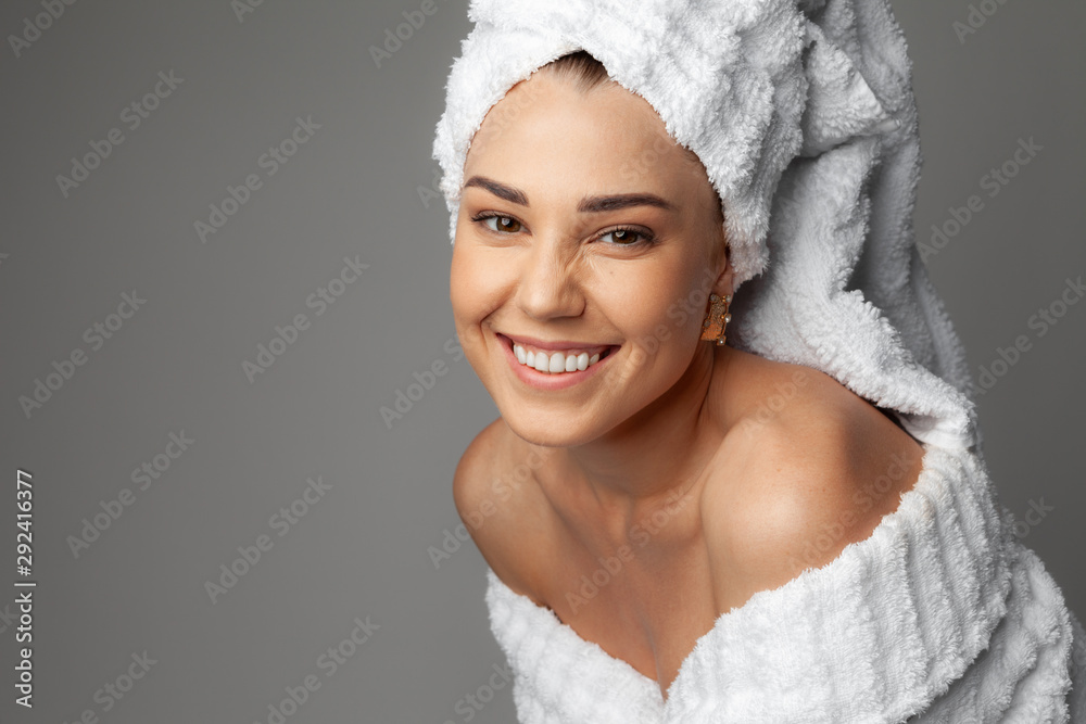Fototapeta Young woman in a bathrobe and towel on her head
