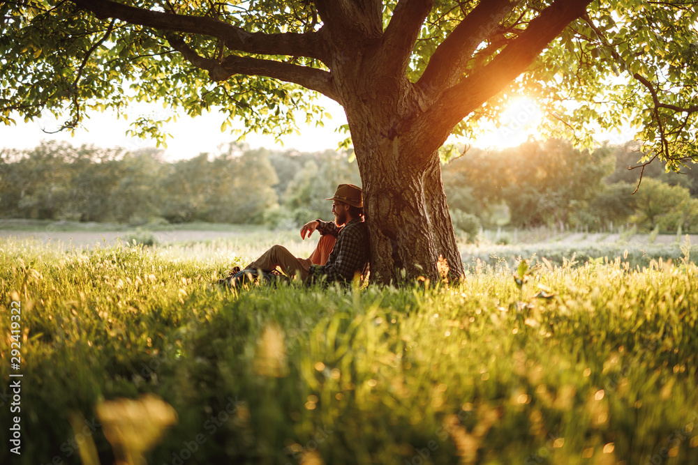 Bearded man relaxing under tree in nature
