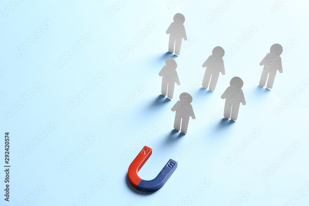 Fototapeta Magnet attracting paper people on light blue background, space for text. Business rivalry concept