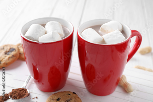Cups of tasty cocoa with marshmallows and cookies on white wooden table