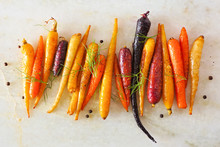 Colorful Roasted Rainbow Carrots Arranged In A Row, Top View Over A White Marble Background