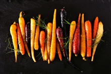 Colorful Roasted Rainbow Carrots Arranged In A Row, Top View Over A Black Stone Background