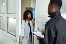 Woman Opening Door To Bailiff