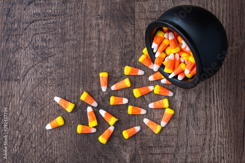 Black ceramic cauldron filled with holiday candy corn tipped over on a rustic wo Billede på lærred