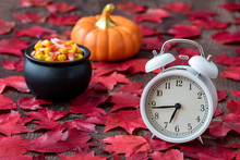 Fall Color In Red Maple Leaves On A Rustic Wood Floor With A White Analog Alarm Clock, Black Cauldron With Candy Corn, And A Ceramic Pumpkin