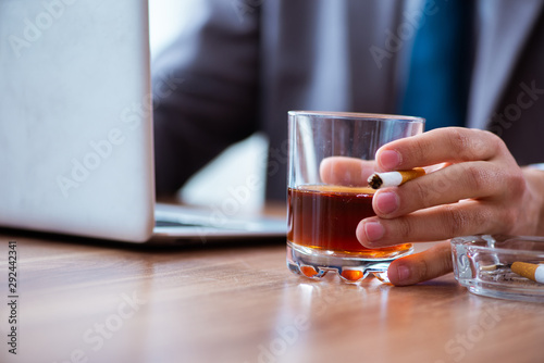 Fotografia  Male employee drinking alcohol and smoking cigarettes at workpla