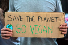 """Activist With """" Save The Planet, Go Vegan"""" Placard At Climate Change Prostest"""