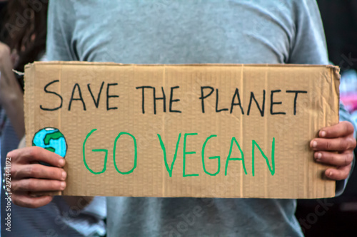 Fotografía Activist with  Save the planet, Go Vegan placard at climate change prostest