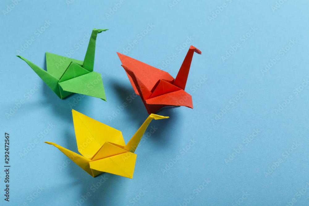 Fototapeta origami paper crane on a blue background