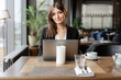 Young woman smile, Sitting in coffee shop at wooden table. On table is gray aluminum laptop. Girl blogging, browsing internet, chatting