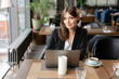 Lovely young woman Sitting in coffee shop. On table is gray aluminum laptop. Girl blogging, browsing internet, chatting in social networks. Uses a wireless Internet connection