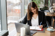 Pretty woman making notes in a notebook. Young businesswoman Sitting in coffee shop at wooden table. On table is gray aluminum laptop. Schedules and makes important notes