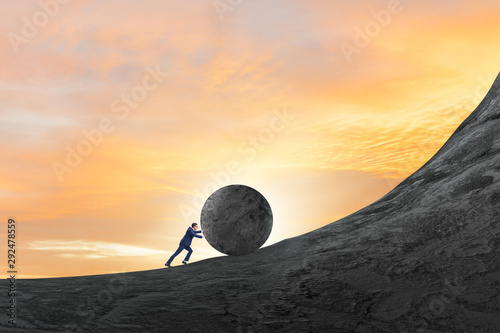 Man pushing large stone to the top - 292478559