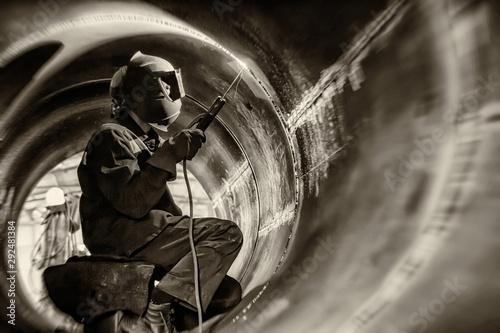 Fotografia  Welding works inside the large diameter heat exchanger housing.