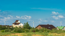 Wind Turbines Behind Houses In Residential Area On Blue Sky Background. Clean And Renewable Energy Concept