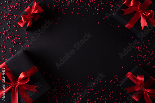 Top view of black christmas boxes with red ribbon on black background with copy space for text. black Friday composition. - 292499532
