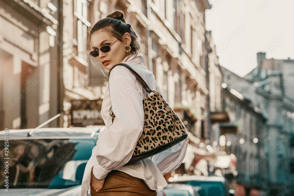 Fototapeta Outdoor autumn fashion portrait of elegant, luxury woman wearing sunglasses, trendy white shirt, leather trousers, with animal, leopard print bag, walking in street of European city. Copy, empty space