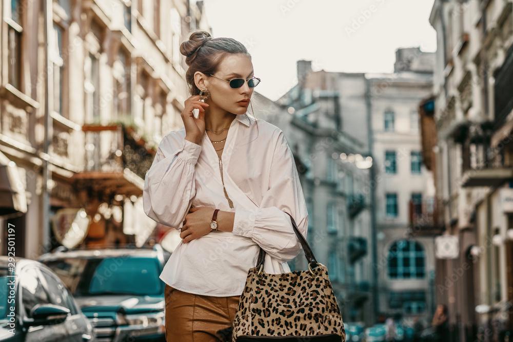 Fototapeta Outdoor autumn fashion portrait of elegant, luxury lady wearing sunglasses, trendy white shirt, wrist watch, holding animal, leopard print bag, posing in street of European city. Copy, empty space